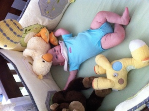 Hanging out in her crib with her giraffe, monkey and duckie